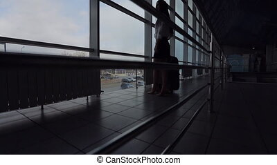 Business woman with luggage stands near windows in airport....