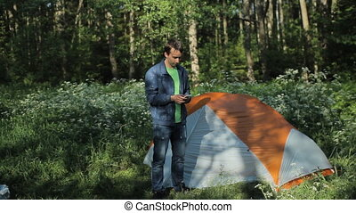The man is touching the phone next to the tent. Early morning in the forest