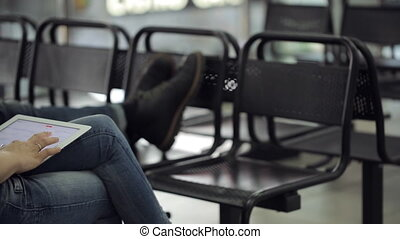 Woman sits on black chair in airport and plays with touchpad