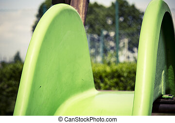 Green child slide on playground, entertaiment tool