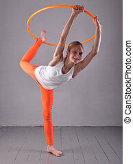Teenage sportive girl is doing exercises with hula hoop t on...