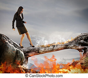 Overcome obstacles - Woman walking on a trunk with flames
