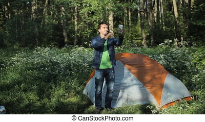 A man makes a video call on the phone. Nearby stands a tent in the forest, early morning