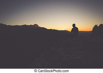 Hiker on a mountain top at sunset. Woman admiring mountain...