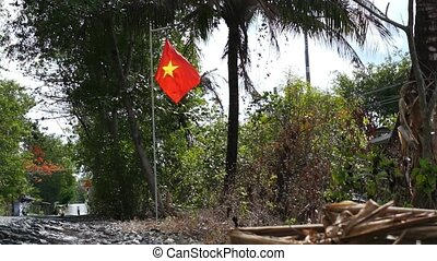 Flag of Vietnam waving on flagpole while motorbike running...