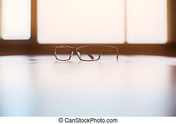 Backlit glasses on bright desktop with window in the...