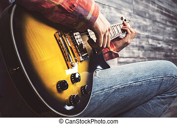 Guy playing guitar - Side view of young casual guy playing...
