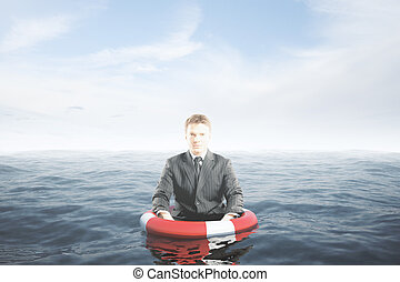 Businessman with lifebuoy ring in water waist-deep....