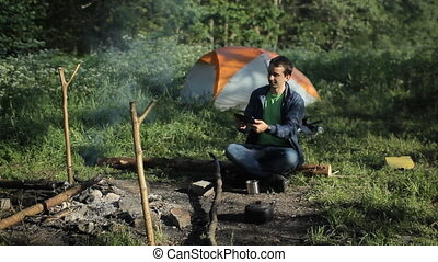 A man taking pictures a fire on the tablet. Against the background is a tent in the forest early in the morning