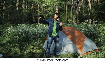 A man makes a video call on the tablet. Nearby stands a tent in the forest, early morning