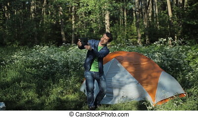 Man making selfie on the tablet. Nearby stands a tent in the forest, early morning