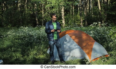 A man playing on a tablet next to the tent in the forest, early morning