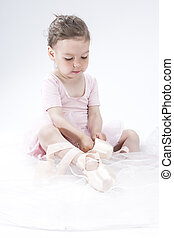 Natural Portrait of Cute Little Ballerina Putting on Mini...
