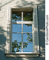 Old renovated window with sky reflections