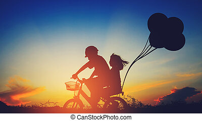Boy with his sister riding bicycle on sunset...