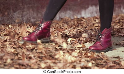 Girl in red shoes kicking fallen le - Slowmotion womans legs...