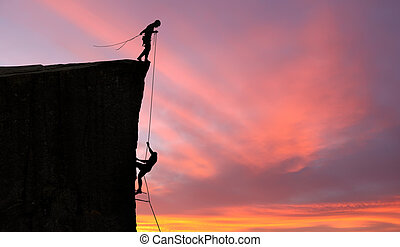 People helping each other to reach top of the mounting -...