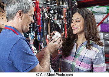 Salesman And Female Customer Playing With Guinea Pig - Happy...