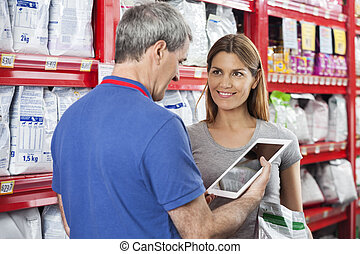 Woman Looking At Salesman Using Digital Tablet In Pet Store...