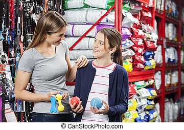 Mother And Daughter Buying Toys In Pet Store - Happy mother...