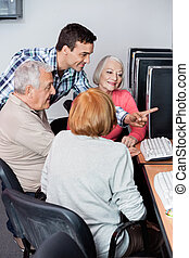 Teacher Assisting Senior Students In Using Computer At Classroom