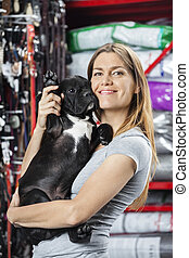 Happy Woman Carrying French Bulldog At Pet Store - Portrait...