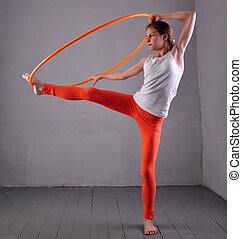 Teenage sportive girl is doing exercises with hula hoop t on grey background. Having fun playing game . Sport healthy lifestyle concept. Sporty childhood. Teenager exercising with tool.
