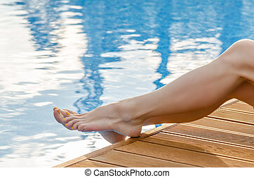 Female legs in the pool water - Female legs on the wooden...