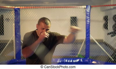 Sportsman doing exercise in a boxing cage 4K