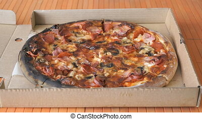 A gesture of a hand, showing fingers up over pizza - The...