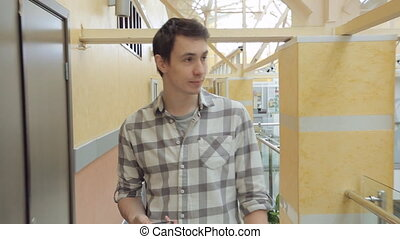 Man in checkered shirt with cell- phone walks through building