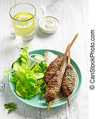 grilled minced meat skewers kebabs on white wooden table