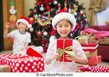 Can I open it yet? - Happy Chinese girl sitting on the floor...