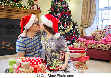 Christmas Morning Kisses - Chinese couple sharing a kiss on...
