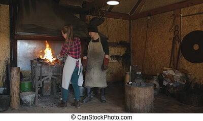 Woman forges with a hammer in forge under supervision of a blacksmith.