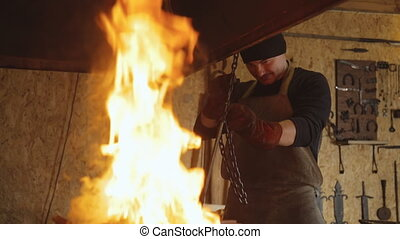Blacksmith puts metal billet on chain in furnace to heat it.