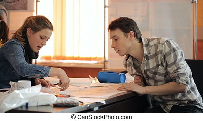 Woman shows man concept on schemes lying on table. Sheets of...