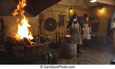Blacksmith forges, standing next to a woman in a furnace of burning fire.