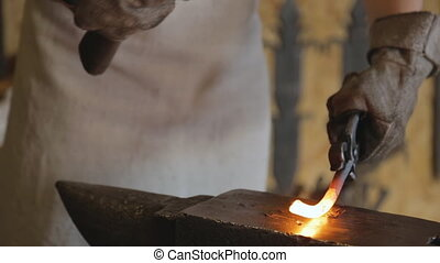 Blacksmith forges blank metal with a hammer, closeup....