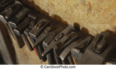 Hand tool for metal forging hangs on wall closeup. Of shaped...