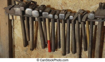 Different hammers hanging on wall for forging a metal...