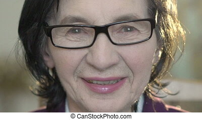 Closeup portrait of happy mature woman's looking on camera. Slowly