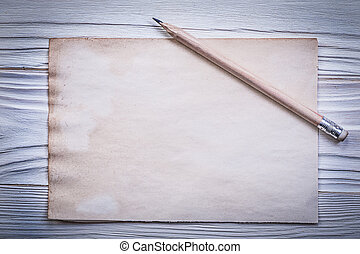 Vintage clean paper sheet pencil on wooden board.
