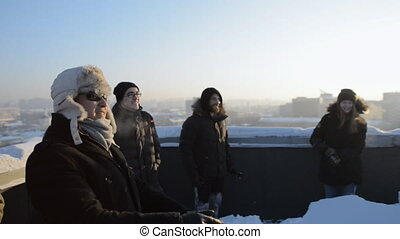 Young people playing snowball game on the roof of a high...