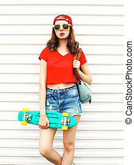 Fashion pretty woman with skateboard in sunglasses and...