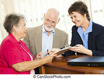 Senior Financial Advice - Sign Here - Senior couple working...