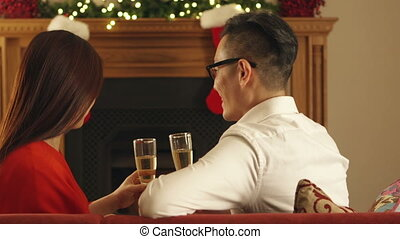 Christmas Champagne Toast - Chinese couple enjoying a glass...