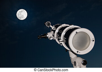 Astronomical telescope over dark sky with the moon in the...
