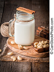 Cashew nut vegan milk non dairy in a glass lar with cashew...