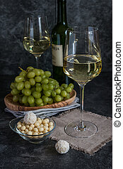 Bottle of white wine, two glasses and bunch of grapes on...